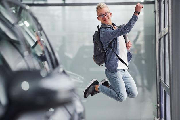Heureux gars hipster sautant à l'intérieur et près de la voiture