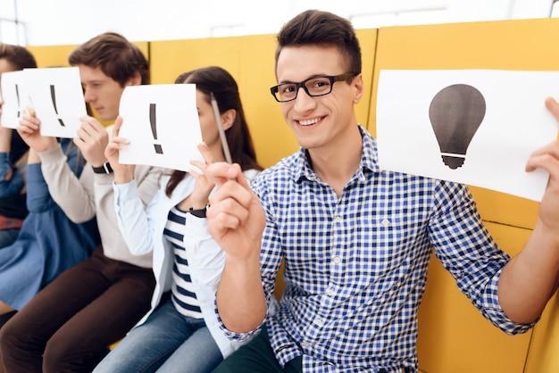 Heureux gars intelligent détient la feuille avec l'image d'avoir une idée assise sur des boîtes.