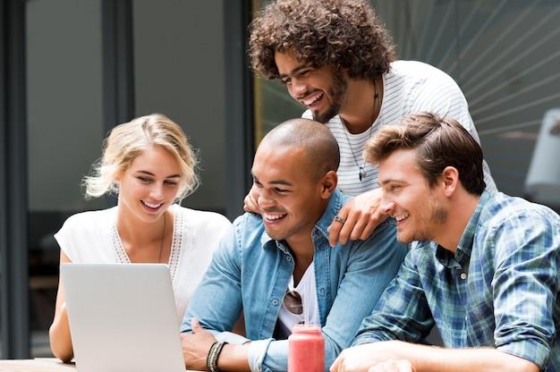 Heureux gars souriant et fille étudiant avec ordinateur portable au café