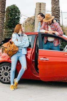 Heureux gens debout près de voiture rouge