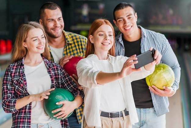 Heureux gens qui posent dans un club de bowling