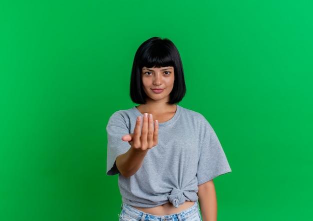 Heureux les gestes de jeune fille caucasienne brune viennent ici avec la main