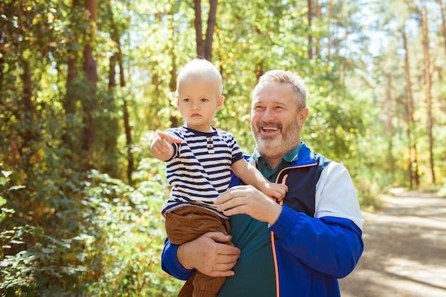 Heureux grand-père et petit-fils pointant du doigt quelque chose au parc d'été