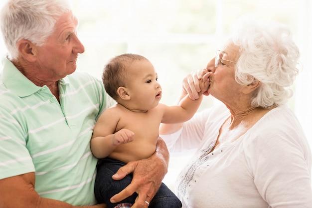 Heureux grands-parents jouant avec leur petit-fils à la maison