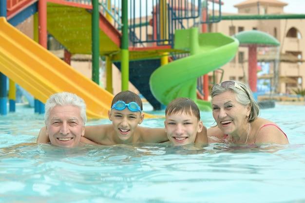 Heureux grands-parents avec leurs petits-enfants dans la piscine en vacances