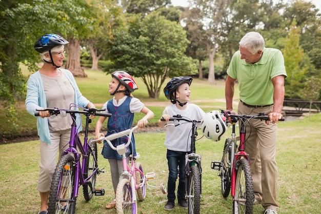 Heureux grands-parents avec leurs petits-enfants sur leur vélo