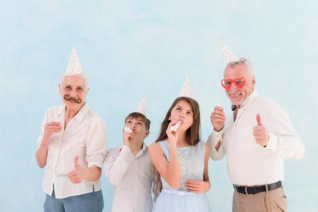 Heureux grands-parents montrant des accessoires en papier avec leurs petits-enfants soufflant dans les cornes d'une fête