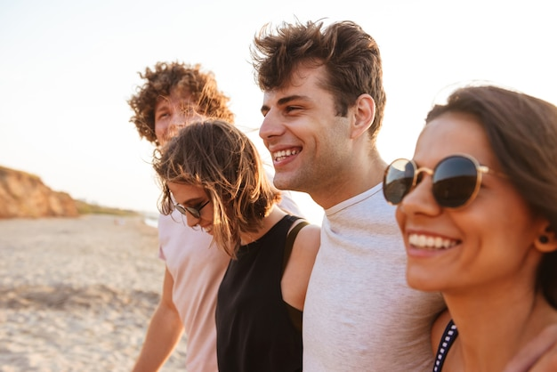 Heureux groupe d'amis aimant les couples marchant en plein air sur la plage en s'amusant