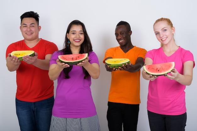 Heureux groupe diversifié d'amis multiethniques souriant et montrant des fruits