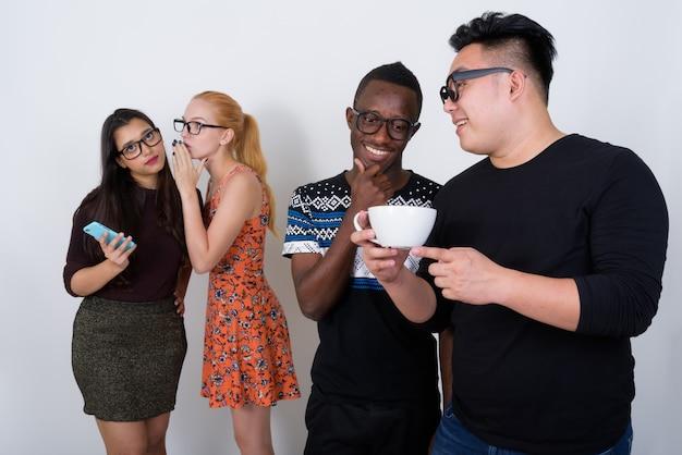 Heureux groupe diversifié d'amis multiethniques souriant tout en ayant une conversation