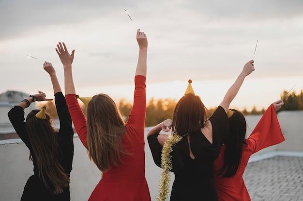 Heureux groupe de femmes admirant le coucher de soleil