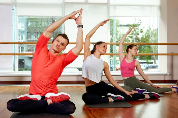Heureux groupe multiracial de jeunes filles souriantes et souriantes et de vitres en vêtements de sport faisant des exercices de yoga en position du lotus. cours de yoga ou de fitness. concept de remise en forme en groupe, séances d'entraînement en groupe, motivation.