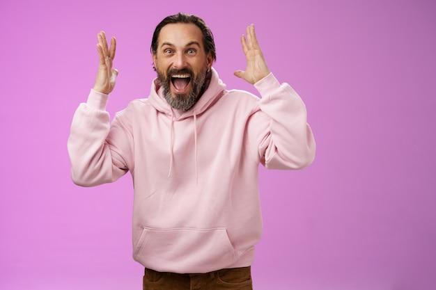Heureux heureux homme barbu adulte chanceux célébrant d'excellentes nouvelles en levant les mains en faisant des gestes ravis souriant broaldy triomphant victoire de la victoire, criant joyeusement atteindre l'objectif, debout fond violet.