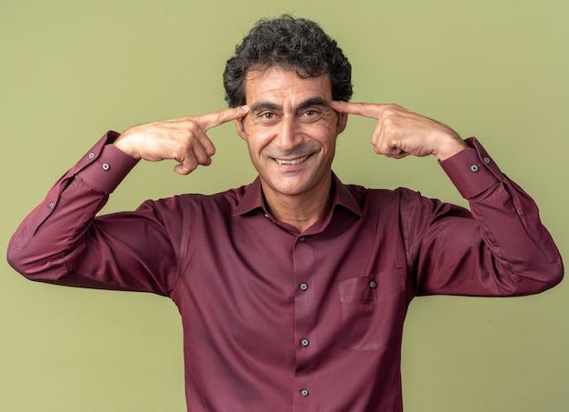Heureux et heureux homme senior en chemise violette pointant vers ses tempes souriant joyeusement debout sur vert