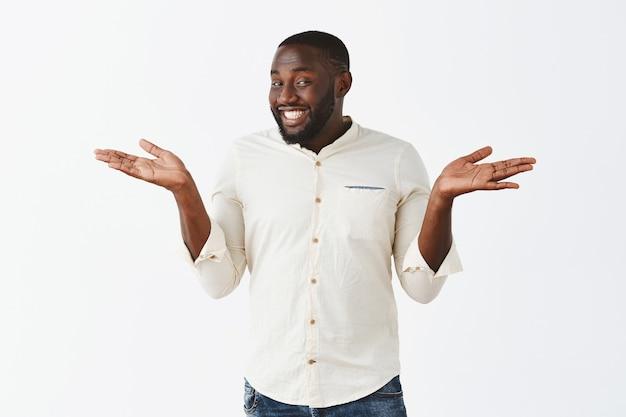 Heureux et heureux jeune homme posant contre le mur blanc