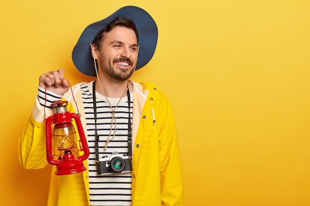 Heureux homme actif tient une lampe à gaz, marche en forêt, porte une caméra rétro sur le cou, regarde avec le sourire de côté, porte un chapeau et un imperméable, pose sur un mur jaune