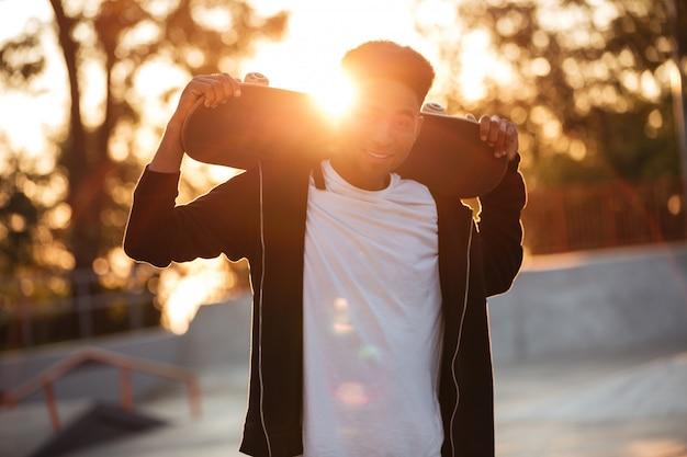 Heureux homme adolescent mâle tenant la planche à roulettes sur les épaules