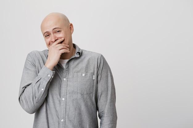 Heureux homme adulte chauve en riant