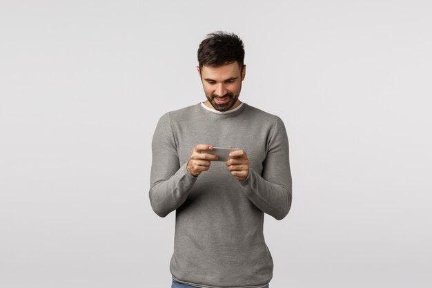 Heureux homme adulte couchait, se sentant excité comme jouant à un nouveau jeu de téléphone génial, tenant le smartphone horizontalement, souriant comme un affichage mobile, téléchargeant des courses ou des arcades