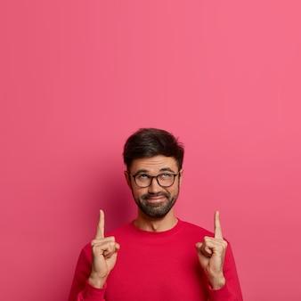 Heureux homme adulte mystérieux avec des poils garde les doigts levés, pointe vers le haut, annonce quelque chose de cool, porte des lunettes et un pull rose, attire votre attention sur un espace vide sur le mur rose