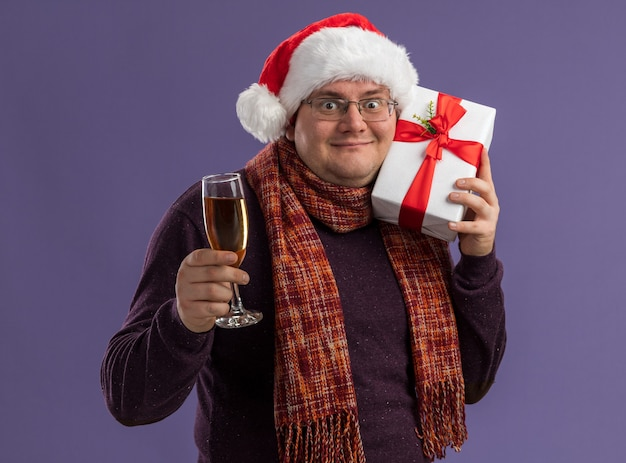 Heureux homme adulte portant des lunettes et un bonnet de noel avec une écharpe autour du cou tenant un verre de champagne et touchant la tête avec un paquet cadeau isolé sur un mur violet