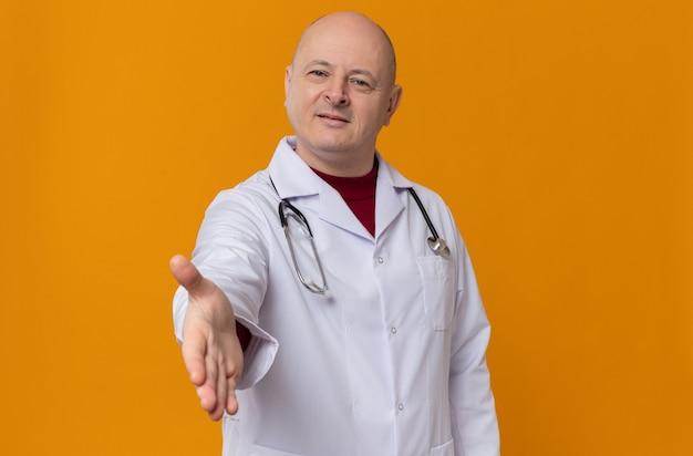 Heureux homme adulte en uniforme de médecin avec stéthoscope tendant la main