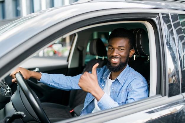 Heureux homme d'affaires africain abandonnant le pouce à l'intérieur de la nouvelle voiture