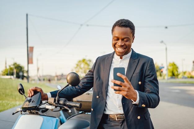 Heureux homme d'affaires africain avec téléphone et vélo à l'extérieur