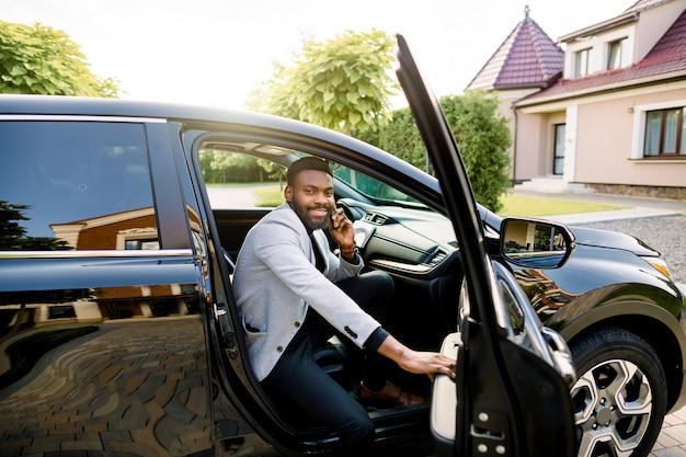 Heureux homme d'affaires afro-américain souriant en costume décontracté intelligent parlant sur smartphone tout en entrant dans la voiture noire sur le siège passager.