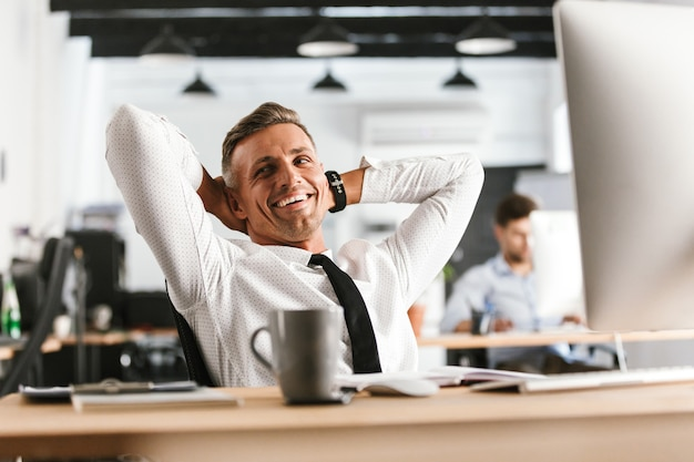 Heureux homme d'affaires d'âge moyen se détendre et regarder ailleurs alors qu'il était assis près de la table au bureau