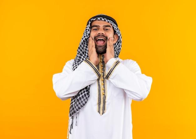 Heureux homme d'affaires arabe en vêtements traditionnels souriant joyeusement debout sur un mur orange