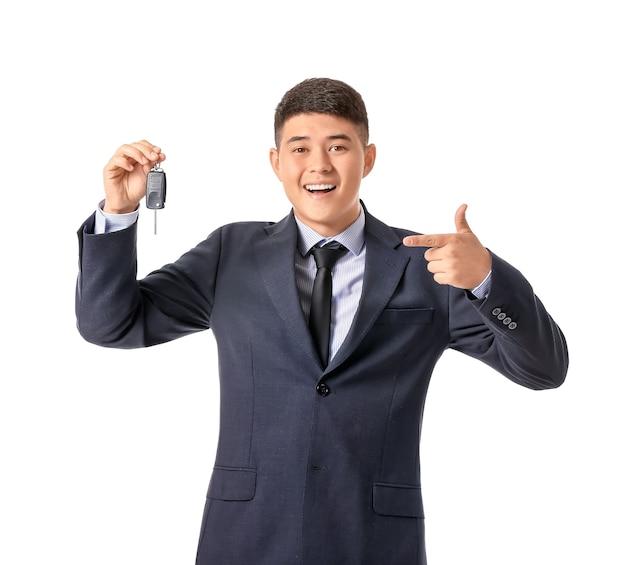 Heureux homme d'affaires asiatique avec clé de voiture isolée