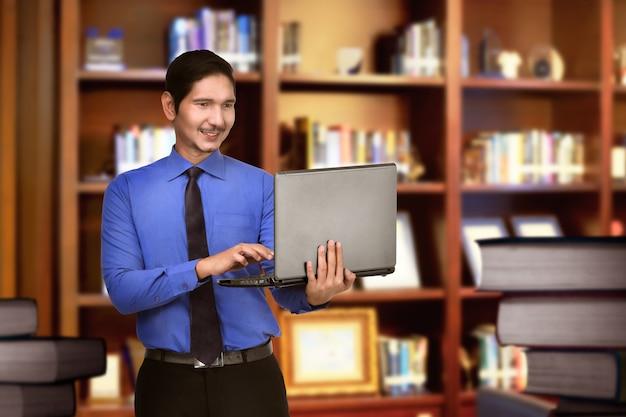 Heureux homme d'affaires asiatique travaillant avec un ordinateur portable