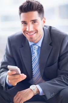 Heureux homme d'affaires assis sur le canapé en envoyant un texte