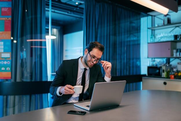 Heureux homme d'affaires ayant une pause café au travail et assis sur le comptoir, buvant du café, utilisant un ordinateur portable.