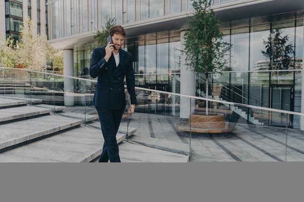 Heureux homme d'affaires caucasien parlant sur smartphone tout en marchant le long du centre de bureaux