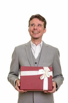 Heureux homme d'affaires caucasien pensant tout en tenant une boîte-cadeau