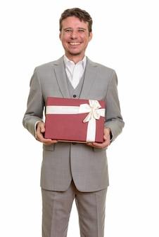 Heureux homme d'affaires caucasien tenant une boîte-cadeau prête pour la saint-valentin