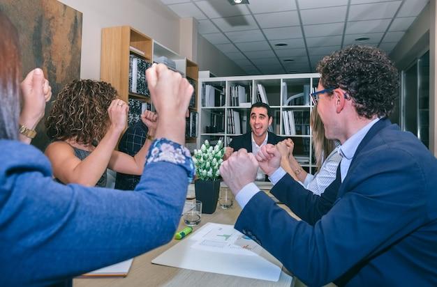 Heureux homme d'affaires célébrant le succès avec le travail d'équipe assis autour d'une table au siège de l'entreprise