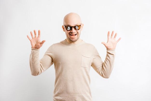 Heureux homme d'affaires chauve avec des signes de bitcoin crypto-monnaie sur des lunettes de soleil. portrait de mineur de blockchain drôle isolé sur blanc.