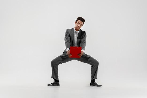 Heureux homme d'affaires dansant en mouvement isolé sur fond de studio blanc. flexibilité et grâce dans les affaires. concept d'émotions humaines. bureau, succès, professionnel, bonheur, concepts d'expression