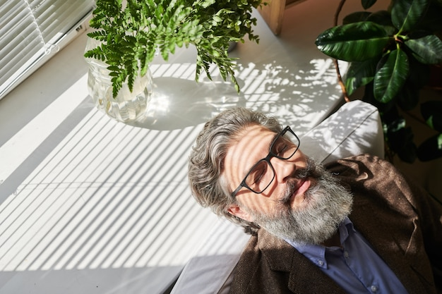 Heureux homme d'affaires détendu mature ou autre professionnel aux cheveux gris et barbe mettant sa tête sur le rebord de la fenêtre après le travail au bureau