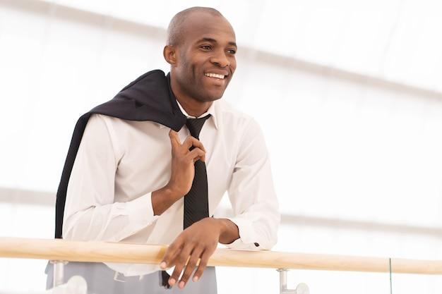 Heureux homme d'affaires. low angle view of joyeux jeune homme africain en chemise et cravate à l'écart et souriant