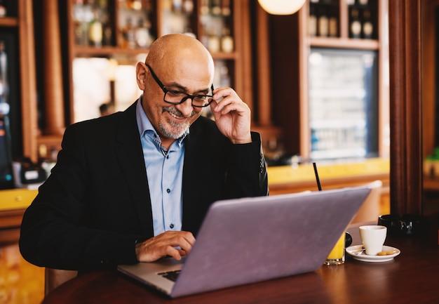 Heureux homme d'affaires mature est assis dans un café et surfer sur internet.