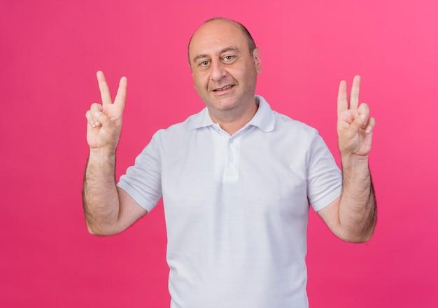 Heureux homme d'affaires mature occasionnel faisant des signes de paix faisant des signes de paix isolés sur fond rose