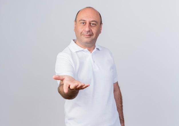 Heureux homme d'affaires mature occasionnel qui tend la main vers la caméra isolé sur fond blanc avec copie espace