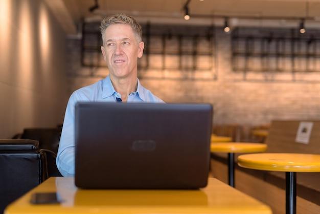 Heureux homme d'affaires mature pensant tout en utilisant un ordinateur portable au café