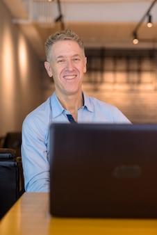 Heureux homme d'affaires mature utilisant un ordinateur portable au café