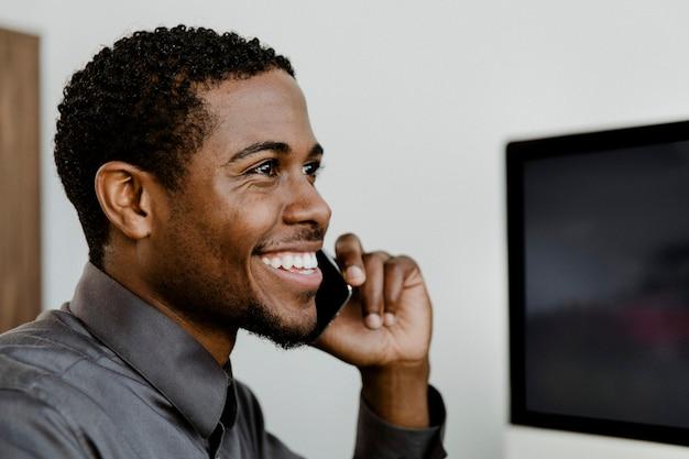Heureux homme d'affaires noir parlant au téléphone