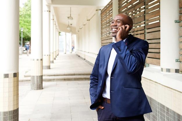 Heureux homme d'affaires parlant au téléphone mobile